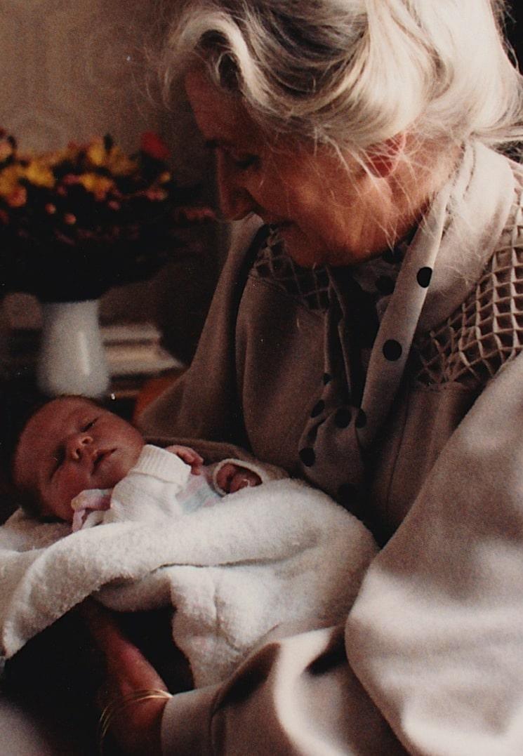 weise und weißhaarige Frau nach dem Klimakterium mit Neugeborenem im Arm