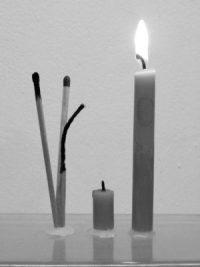 Brennende Kerze neben abgebrannter Kerze daneben Streichholz neu, Streichholz , das kurz brannte und abgebranntes Streichholz